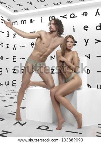beautiful man and woman Adam and Eve, posing in the room with the alphabet on the walls of the white cubes - stock photo