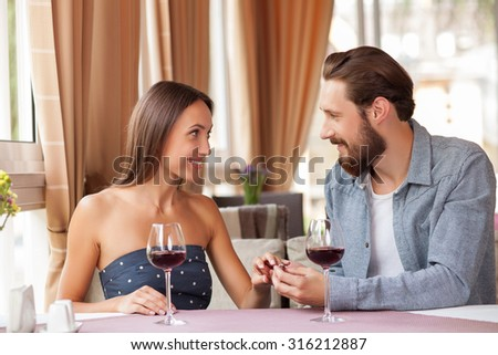 Beautiful man and woman are sitting and drinking wine in cafe. The man is giving a ring to his girlfriend and wearing in on her finger. They are looking at each other and smiling - stock photo