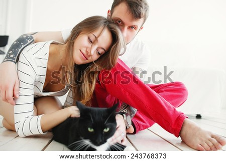 Beautiful man and woman in a white interior with a black cat - stock photo
