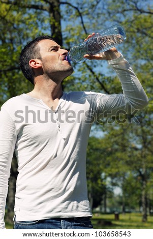 beautiful man drinking water in a park - stock photo