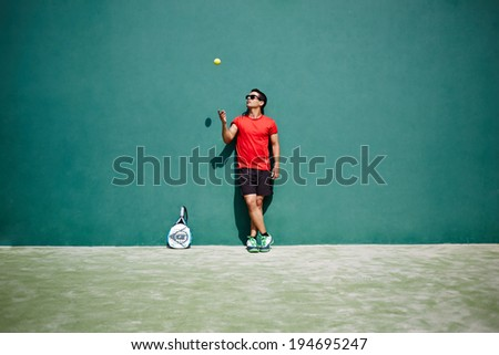 Beautiful man playing paddle tosses the ball - stock photo