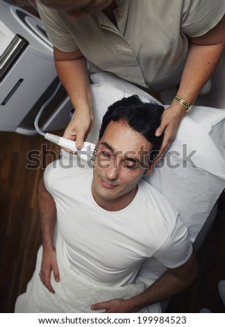 Beautiful man with closed eyes having a laser skin treatment in a skincare clinic, male patient lying on the medical chair at rejuvenation procedure in aesthetic clinic - stock photo