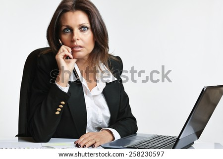 Beautiful manager woman at her working desk with laptop. White backdrop - stock photo