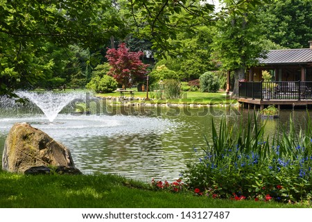 Beautiful manicured garden with a deck overlooking a pond with a fountain that's surrounded with potted plants and flower beds. - stock photo