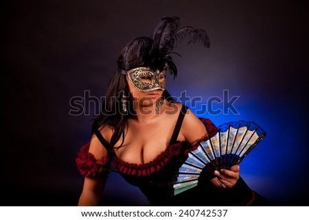 Beautiful masked young woman on black background - stock photo