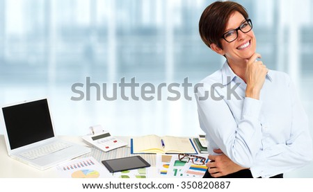 Beautiful mature business woman over blue office background. - stock photo