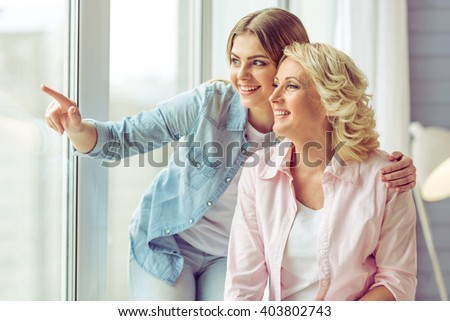 Beautiful mature mother and her daughter hugging, looking out the window and smiling while sitting at home - stock photo