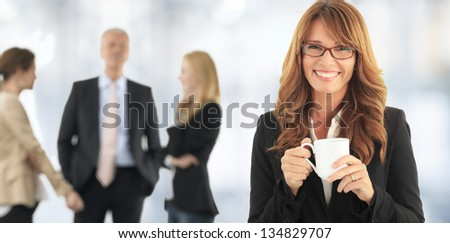 Beautiful mature woman drinking a cup of coffee. With her colleagues In background. - stock photo