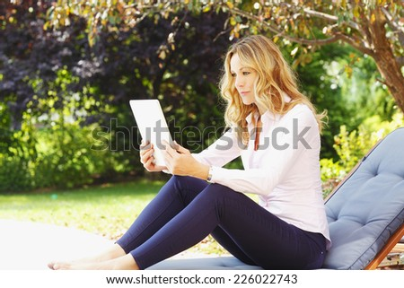 Beautiful mature woman holding digital tablet her hands and sitting at garden.  - stock photo