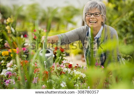 Beautiful mature woman in a garden watering flowers - stock photo