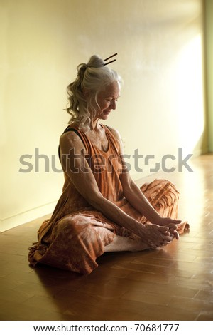 Beautiful mature woman in yoga pose baddhakonasana. - stock photo
