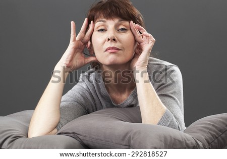 beautiful mature woman lifting her eyes naturally relaxing on grey cushions for concept of anti-aging skincare - stock photo