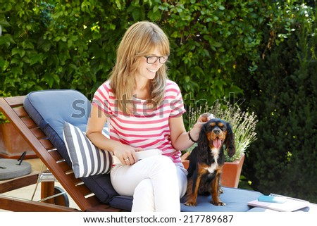 Beautiful mature woman sitting in garden with her spaniel puppy.  - stock photo