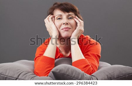 beautiful mature woman smiling, relaxing on her bed with hands on cheeks, thinking in being laid down, wearing colorful sweater - stock photo