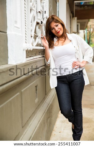 Beautiful mature woman standing at a metal window in an urban environment. - stock photo