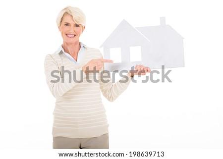 beautiful mature woman woman pointing white paper house - stock photo