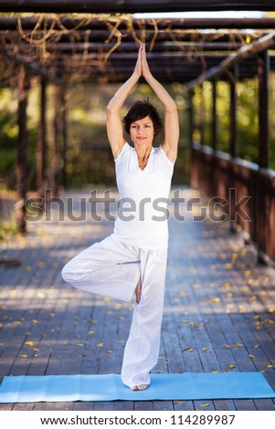 beautiful mature woman yoga pose in garden - stock photo
