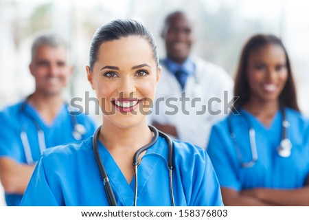 beautiful medical nurse and colleagues in hospital - stock photo