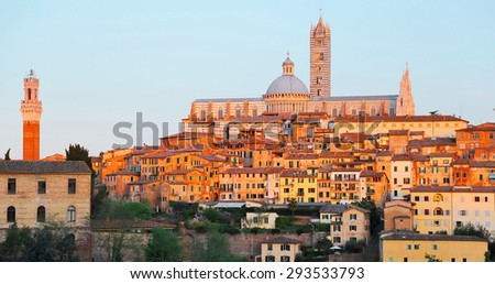 Beautiful medieval town of Siena with view of Mangia Tower, Duomo Dome and Bell Tower bathed in golden sunlight at sunset ~ Romantic scenery of Siena at rosy dusk, in Tuscany, Italy Europe - stock photo