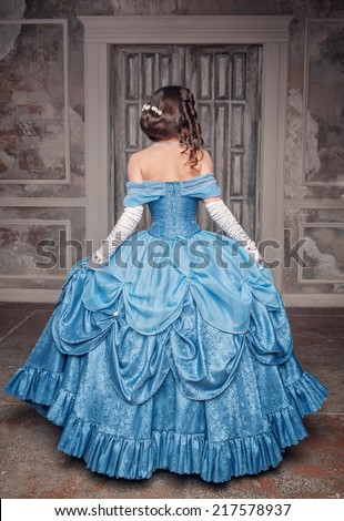 Beautiful medieval woman in long blue dress, back  - stock photo