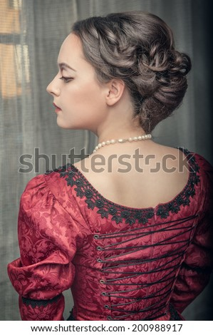 Beautiful medieval woman in red dress  - stock photo