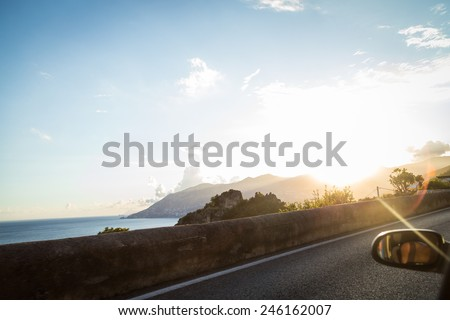 Beautiful Mediterranean landscape from the window of the car. Sunset in the coastal seaside town. Sea Sunset View from the road for cars. - stock photo