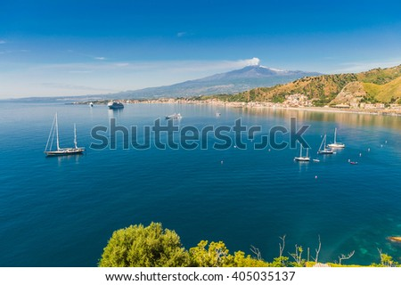 Beautiful mediterranean sicilian coastal landscape with cruising boats view from Taormina with the mount Etna in the background, Sicily, Italy - stock photo