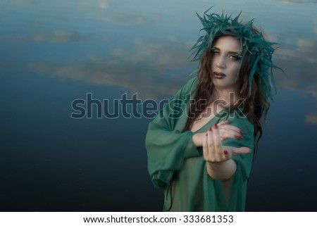 Beautiful mermaid on the forest lake - stock photo