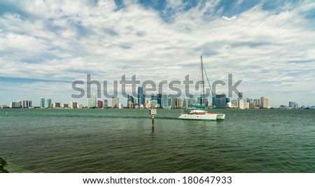 Beautiful Miami skyline along Biscayne Bay with sailboat cruising by. - stock photo
