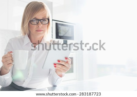 Beautiful mid adult businesswoman having coffee while using table PC at home - stock photo