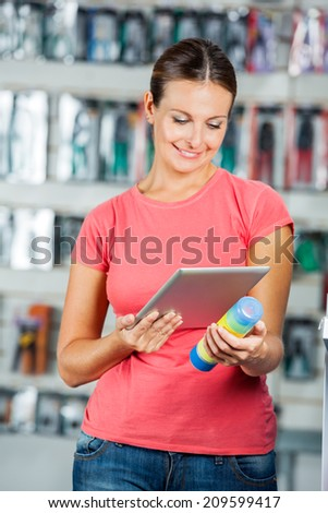 Beautiful mid adult woman scanning product's barcode through digital tablet in hardware store - stock photo