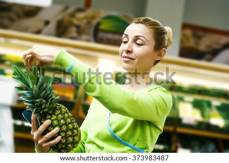 Beautiful mid adult woman shopping for fruits in a supermarket - stock photo