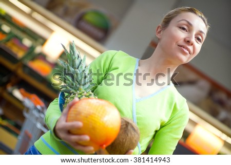 Beautiful mid adult woman shopping for fruits in a supermarket. Horizontal shot.  - stock photo