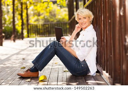 beautiful mid age woman using tablet computer outdoors - stock photo