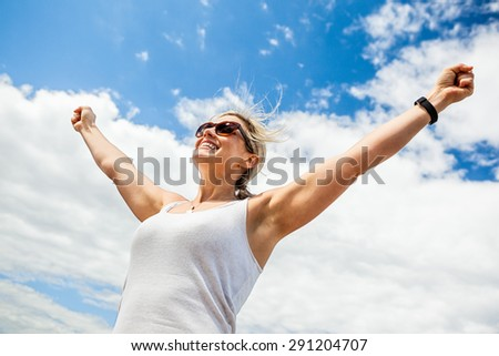 Beautiful mid 30s carefree woman with arms outstretched against a blue sky on a sunny day - stock photo