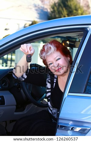 Beautiful middle age women sitting in the car and holding the car keys - stock photo