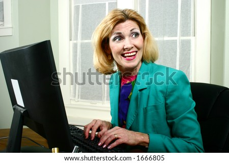 Beautiful middle aged executive business woman laughing with off-stage co-workers while typing on her computer in the office. - stock photo