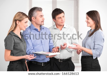 Beautiful middle aged female shearing her opinion with business team. Stylish successful business people in modern office   - stock photo