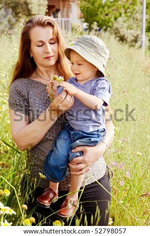 beautiful middle aged grandmother with naturally red hair with her toddler grandson in the green grass field - stock photo