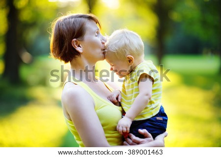 Beautiful middle aged woman and her adorable little grandson at sunny park - stock photo