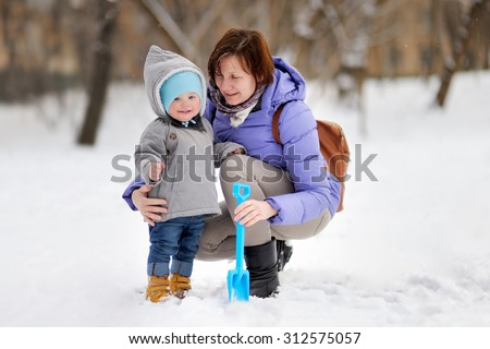 Beautiful middle aged woman and her adorable little grandson at the winter park  - stock photo