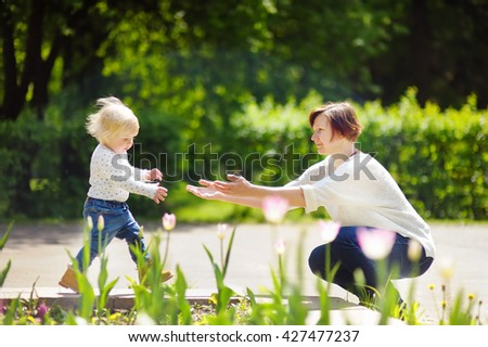 Beautiful middle aged woman and her adorable little grandson walking in sunny park - stock photo