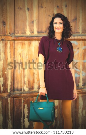 beautiful middle-aged woman in a burgundy dress and green handbag near aged doors. instagram image filter retro style - stock photo