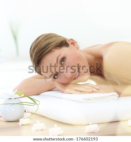 Beautiful middle-aged woman relaxing on massage bed - stock photo