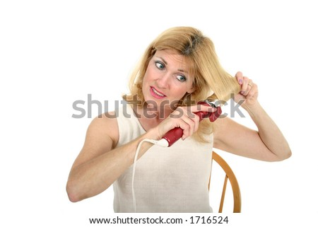 Beautiful middle-aged woman using a curling iron to put curls in her hair. - stock photo