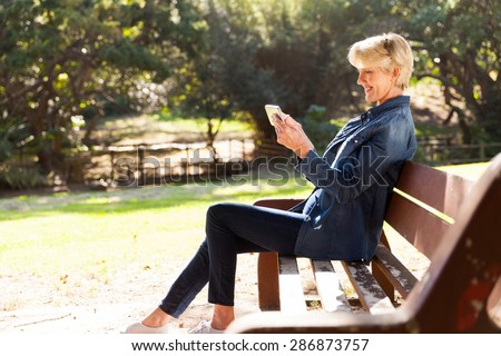 beautiful middle aged woman using smart phone outdoors - stock photo