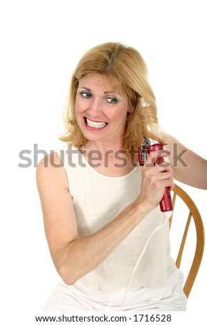 Beautiful middle-aged woman with a pained expression from tangles while using a curling iron to put curls in her hair. - stock photo