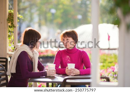 Beautiful middle aged woman with her grown up daughter spending time together and talking in an outdoor cafe  - stock photo