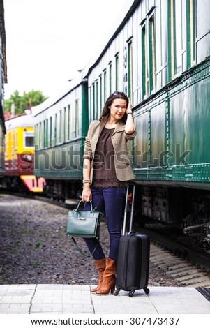 beautiful middle-aged woman with luggage near the old train. retro trip - stock photo