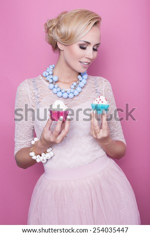 Beautiful middle aged women hold colorful sweets. Soft colors. Studio portrait over pink background - stock photo